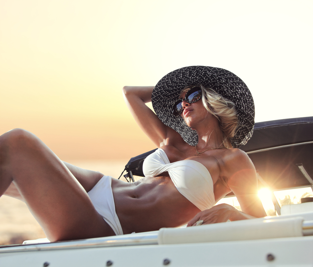 Young sexy woman in white bikini enjoying the sunset on her yacht.