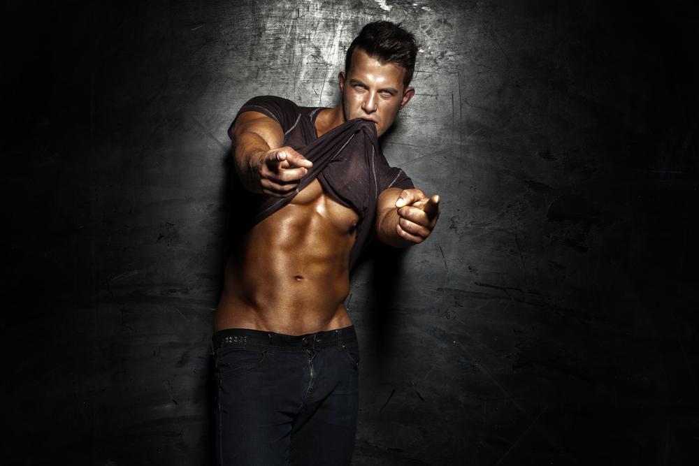 Very_muscular_handsome_sexy_guy_posing_on_dark_background_by_PawelSierakowski_unter_Verwendung_Lizenz_Shutterstock.com