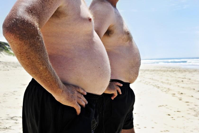 Two_big_men_showing_their_bellies_on_the_beach_by_Tish1_unter_Verwendung_Lizenz_Shutterstock.com