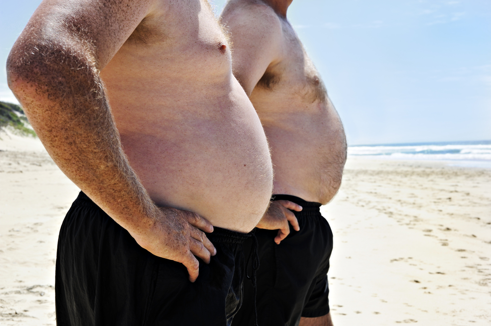 Two_big_men_showing_their_bellies_on_the_beach_by_Tish1_unter_Verwendung_Lizenz_Shutterstock.com